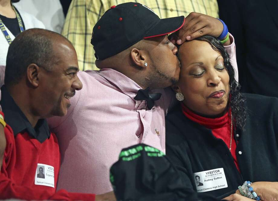 Eugene Sutton kisses his mother Audrey Sutton as father Eugene Sutton looks on during national signing day at Clemens High School in Schertz on February 5, 2014. Photo: TOM REEL