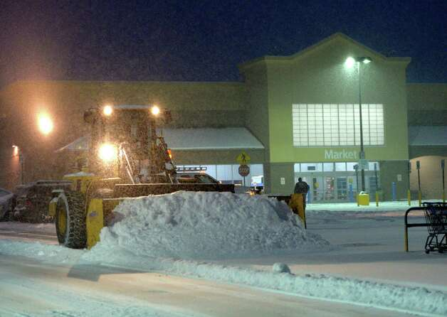 A snow plow works in the heavy snow early Wednesday morning Feb. 5, 2014, at the Walmart Plaza  in Halfmoon, N.Y. (Skip Dickstein / Times Union) Photo: SKIP DICKSTEIN / 00025615A
