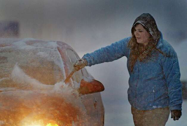 Crystal Maylath removes snow from her car early Wednesday morning Feb. 5, 2014, after her overnight shift at the Walmart Plaza in Halfmoon, N.Y.        (Skip Dickstein / Times Union) Photo: SKIP DICKSTEIN / 00025615A
