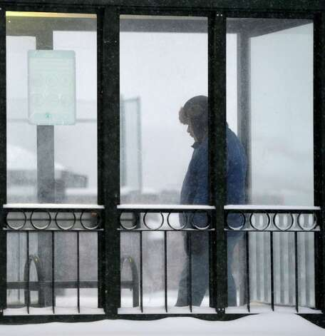 A commuter takes refuge in a bus shelter  Wednesday morning, Feb. 5, 2014, in Latham, N.Y. (Skip Dickstein / Times Union) Photo: SKIP DICKSTEIN / 00025615A
