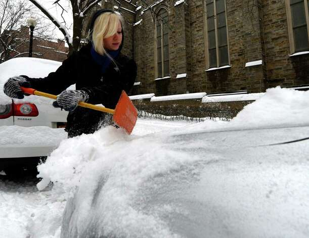 Ashley Dzingle, 24, removes snow from her car on Lancaster Street Wednesday afternoon Feb. 5, 2014, in Albany, N.Y.         (Skip Dickstein / Times Union) Photo: SKIP DICKSTEIN / 00025615A
