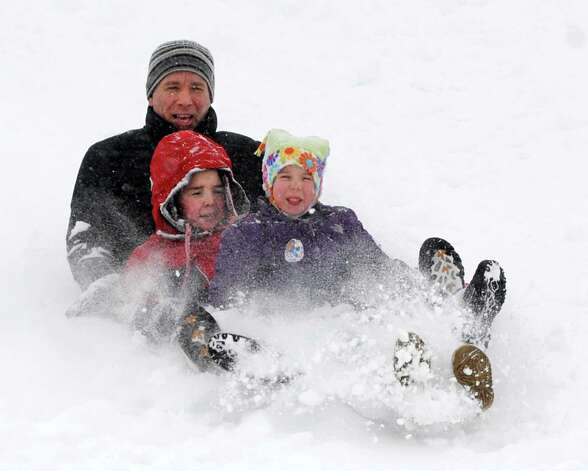 From left, Dan Mahoney of Albany enjoys the fresh snow with his son Ryan, 9, and niece Molly Len, 6, Wednesday, Feb. 5, 2014, at Capital Hills Golf Course in Albany, N.Y.  (Lori Van Buren / Times Union) Photo: Lori Van Buren / 00025615A