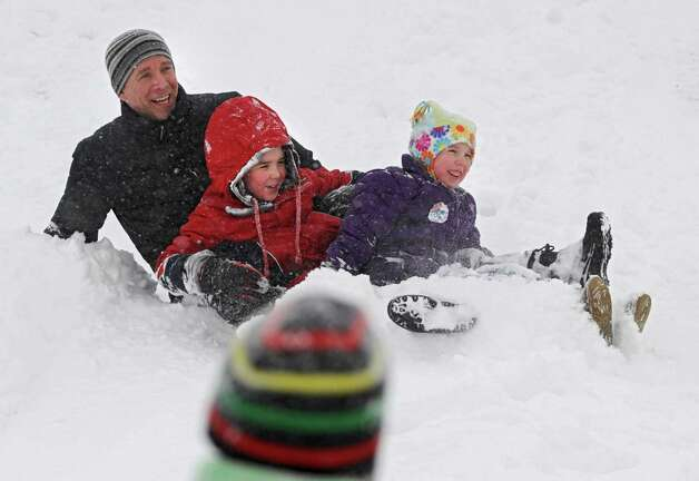 From left, Dan Mahoney of Albany enjoys the fresh snow with his son Ryan, 9, and niece Molly Len, 6,  Wednesday, Feb. 5, 2014, at Capital Hills Golf Coursein Albany, N.Y.  (Lori Van Buren / Times Union) Photo: Lori Van Buren / 00025615A