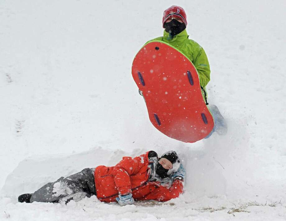 Will Bulmer, 12, of Albany, flies over his friend Danny Warnick, 10, of Albany with the help of a self-made jump Wednesday, Feb. 5, 2014, at Capital Hills Golf Course in Albany, N.Y.  (Lori Van Buren / Times Union) Photo: Lori Van Buren / 00025615A
