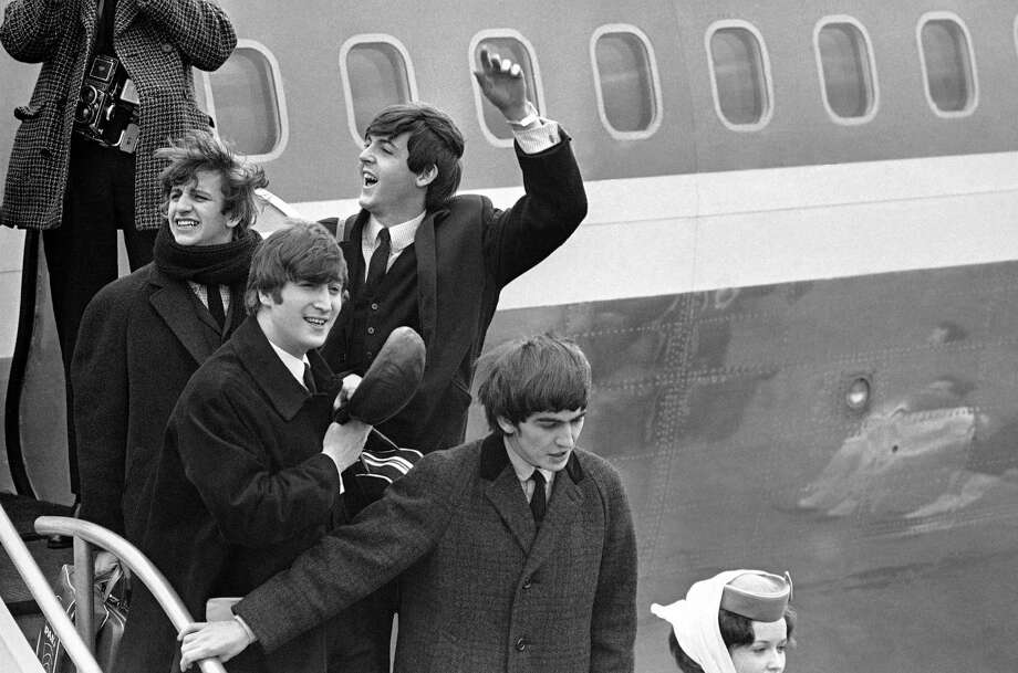 FILE - Britain's Beatles make a windswept arrival in New York in this  Feb. 7, 1964 file photo, as they step down from the plane that brought them from London, at Kennedy airport. From left to right, Ringo Starr, John Lennon, Paul McCartney and George Harrison. One of the most tumultuous welcomes in pop history is to be recreated next month when UK officials and a tribute band recreate the Beatles' historic 1964 landing at JFK airport, in a bid to spark interest in Beatles-related tourism to Britain.  (AP Photo, File) ORG XMIT: LON102 / AP