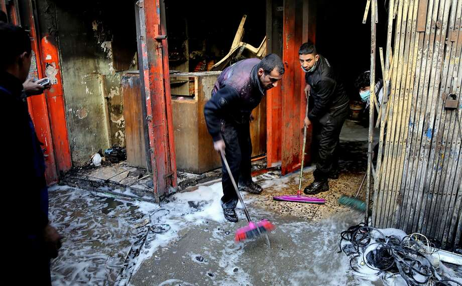 Two men clean up after a bombing at a commercial center in central Baghdad. Multiple blasts hit the district, striking mainly near the fortified Green Zone where key government offices are located. Photo: Karim Kadim, Associated Press