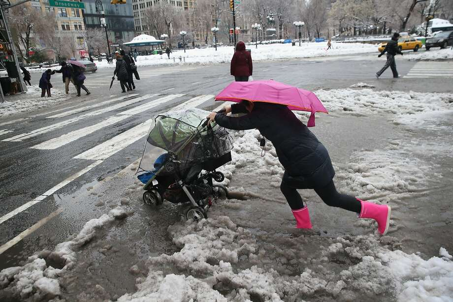 A nanny pushes a stroller through the slushy intersection of Broadway and 14th Street at Union Square in New York City. The onslaught of snow has led to shortages of everything from road salt to blood. Photo: John Moore, Getty Images