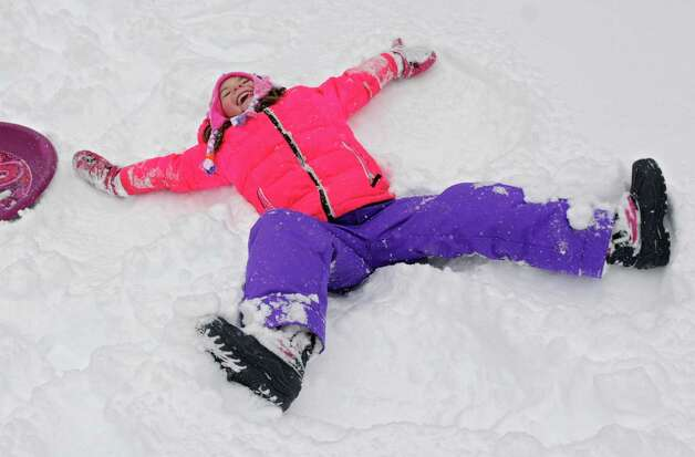 Natalie Conaway, 5, of Guilderland takes a break from sledding to make a snow angel in her front yard during Wednesday's snowstorm, Feb. 5, 2014, in Guilderland, N.Y.  (Lori Van Buren / Times Union) Photo: Lori Van Buren / 00025615A