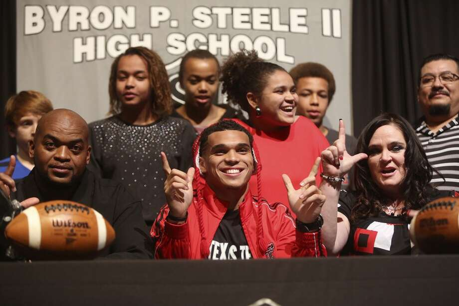 Justin Stockton celebrates after signing to play football for Texas Tech with his family including his father, Eric Harris, left, and mother, Melissa Stockton, right, on National Signing Day at Steele High School in Cibolo on Wednesday, Feb. 5, 2014. Photo: Lisa Krantz
