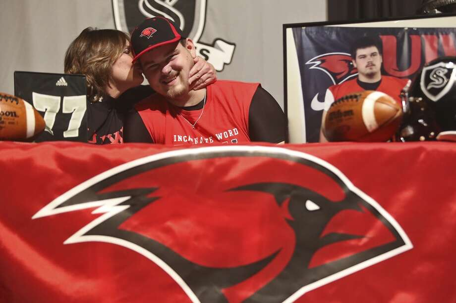 Cameron Jackson gets a kiss from his mom, Darcy Jackson, before signing to play football for Incarnate Word University on National Signing Day at Steele High School in Cibolo on Wednesday, Feb. 5, 2014. Photo: Lisa Krantz