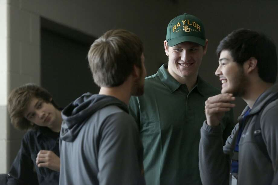 Joshua Malin, celebrates with friends as his brother, Sonny Kohlenberg, 13, left, watches after Malin signed to play football at Baylor on National Signing Day at Steele High School in Cibolo on Wednesday, Feb. 5, 2014. Photo: Lisa Krantz