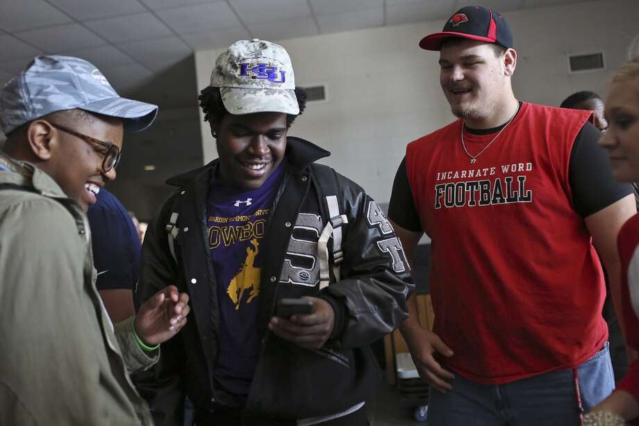 Sterling Jenkins, who signed to play football for Howard Payne University, from left, Kenneth Wise, who signed to play for Hardin Simmons University, and Cameron Jackson, who signed to play for Incarnate Word, celebrate on National Signing Day at Steele High School in Cibolo on Wednesday, Feb. 5, 2014. Photo: Lisa Krantz