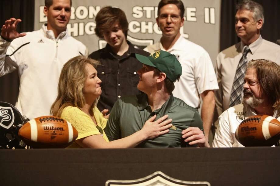 Joshua Malin, center, looks back at head coach Scott Lehnhoff, far left, after signing to play football at Baylor on National Signing Day at Steele High School in Cibolo on Wednesday, Feb. 5, 2014. With Malin are his parents, Roxanne and David Kohlenberg and his brother, Sonny Kohlenberg, 13. Photo: Lisa Krantz