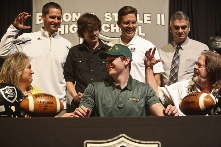 Joshua Malin, center,  celebrates signing to play football at Baylor on National Signing Day at Steele High School in Cibolo on Wednesday, Feb. 5, 2014. With Malin are his parents, Roxanne and David Kohlenberg, brother, Sonny Kohlenberg, 13, and head coach Scott Lehnhoff, far left. Photo: Lisa Krantz