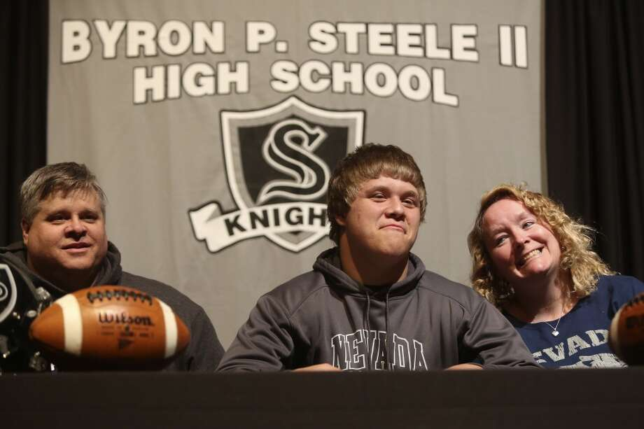 Matthew Moen sits with his parents, David and Jill Moen, after signing to play football for Nevada on National Signing Day at Steele High School in Cibolo on Wednesday, Feb. 5, 2014. Photo: Lisa Krantz