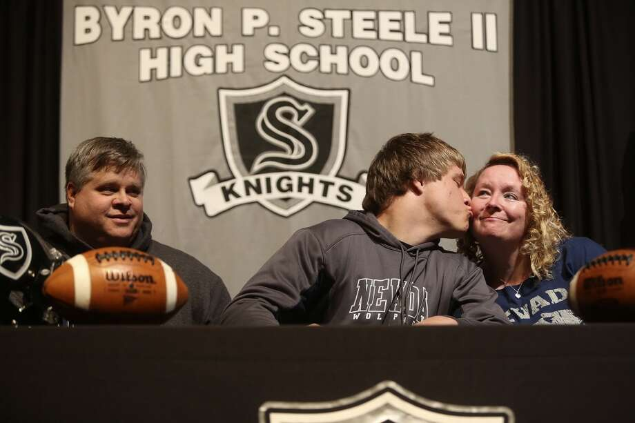 Matthew Moen kisses his mom, Jill Moen, with his father, David Moen, left, after signing to play football for Nevada on National Signing Day at Steele High School in Cibolo on Wednesday, Feb. 5, 2014. Photo: Lisa Krantz