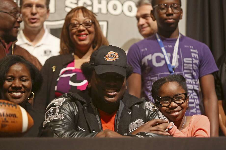 Deionte Noel celebrates signing to play football for Oklahoma State University with his family including his mother, Leslie Noel, left, sister, Samantha Noel, 9, and behind him, his grandparents, Charlie and Brenda Johnson, and his brother, Justin Noel, 14, on National Signing Day at Steele High School in Cibolo on Wednesday, Feb. 5, 2014. Photo: Lisa Krantz