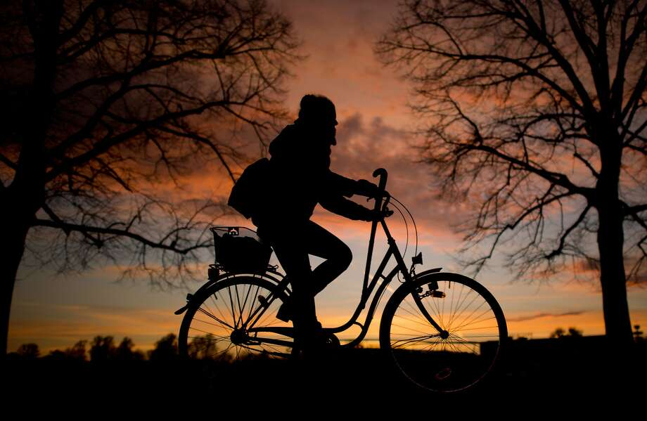 A bicyclist rides offinto the sunset in Hanover, Germany. Photo: Julian Stratenschulte, Associated Press
