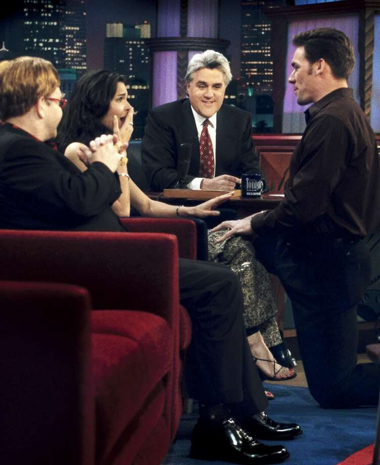 "As Elton John and Jay Leno look on, then-professional football player Jason Sehorn, proposes to actress Angie Harmon on ""The Tonight Show with Jay Leno"" on March 13, 2000. Photo: Paul Drinkwater"