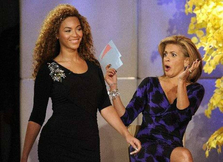 "The star surprises ""Today"" show co-host Hoda Kotb while modeling one of Tina Knowles' designs. (AP Photo/NBC, Peter Kramer)"