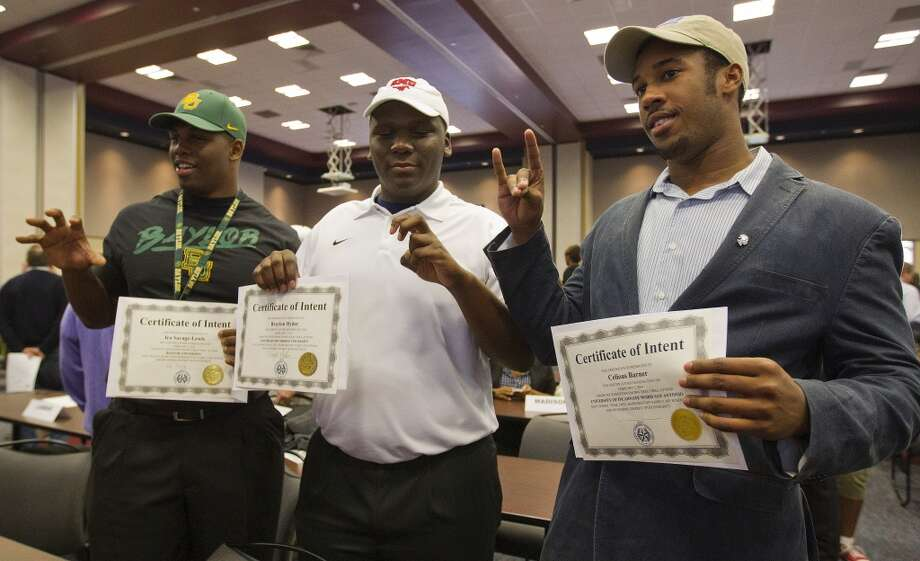 Lamar's Ira Savage-Lewis, left, signed with Baylor, gets his photo taken with teammate Braylon Hyder, who signed with SMU and Celious Barner, who signed with Incarnate Word, San Antionio signing day event. Photo: Karen Warren, Houston Chronicle
