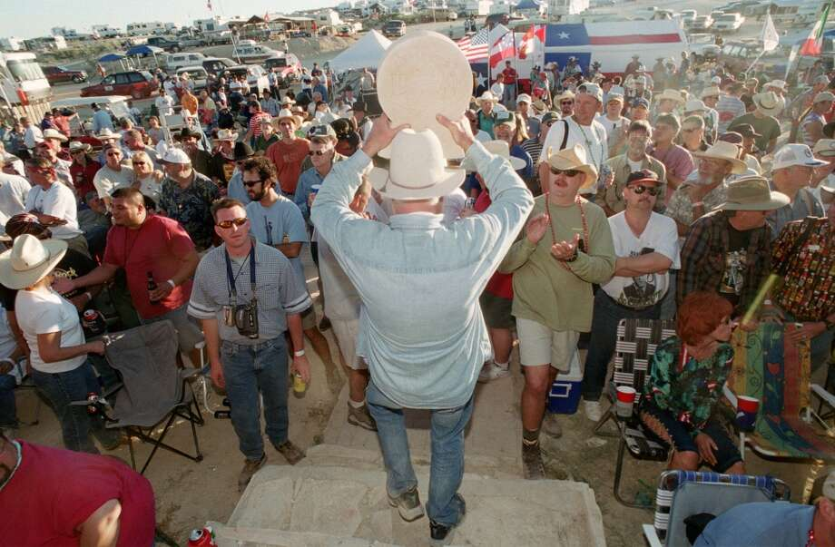 "Grand Prize winner Clifton Dugan from Denison and ""Red Rat Chili"" holds his award high as he walks thru the crowd at the Original Championship Chili Cook-off in Terlingua.  11/01/2002  (E. Joe Deering/Chronicle).  Photo: Houston Chronicle"