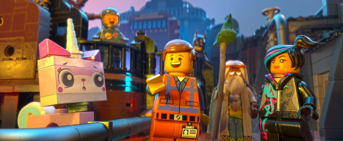 """(L-r) LEGO- characters Unikitty (voiced by ALISON BRIE), Benny (CHARLIE DAY), Emmet (CHRIS PRATT), Batman (WILL ARNETT), Vitruvius (MORGAN FREEMAN) and Wyldstyle (ELIZABETH BANKS) in the 3D computer animated adventure """"The LEGO Movie,"""" from Warner Bros. Pictures, Village Roadshow Pictures and Lego System A/S. A Warner Bros. Pictures release."""