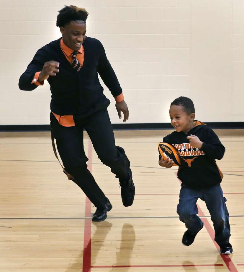 Derick Roberson, left, of Brennan High School, plays with his brother Torian Roberson, 5, before the signing ceremony at the high school. Roberson signed with the University of Texas football team.  Also signing from Brennan are Tanner Hanssen going to Southwestern University and Nathaniel Wells Jr. going to Northwestern Oklahoma. Wednesday, Feb. 5, 2014. Photo: San Antonio Express-News