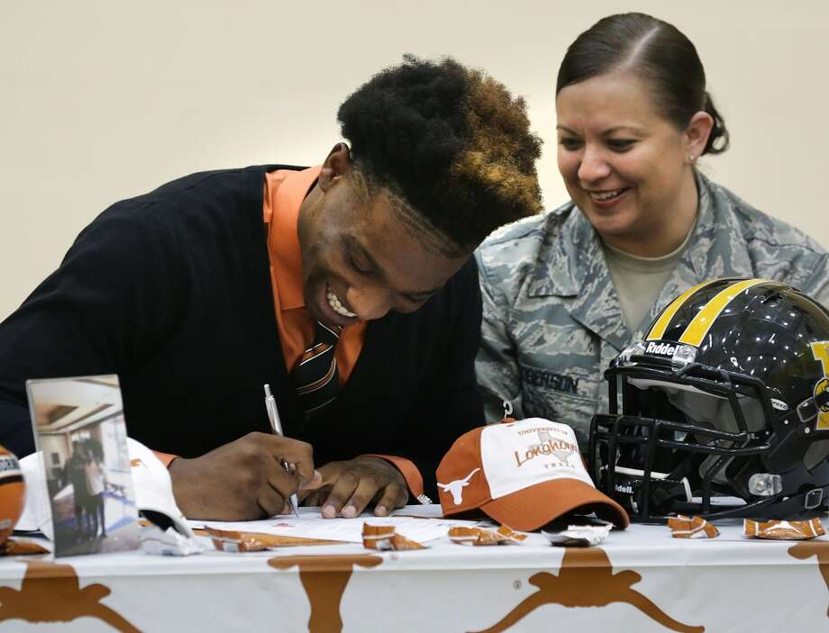 Derick Roberson, of Brennan High School, signs with the University of Texas football team, as his mother, Kim Roberson, right, looks on.   Wednesday, Feb. 5, 2014. Photo: BOB OWEN, San Antonio Express-News