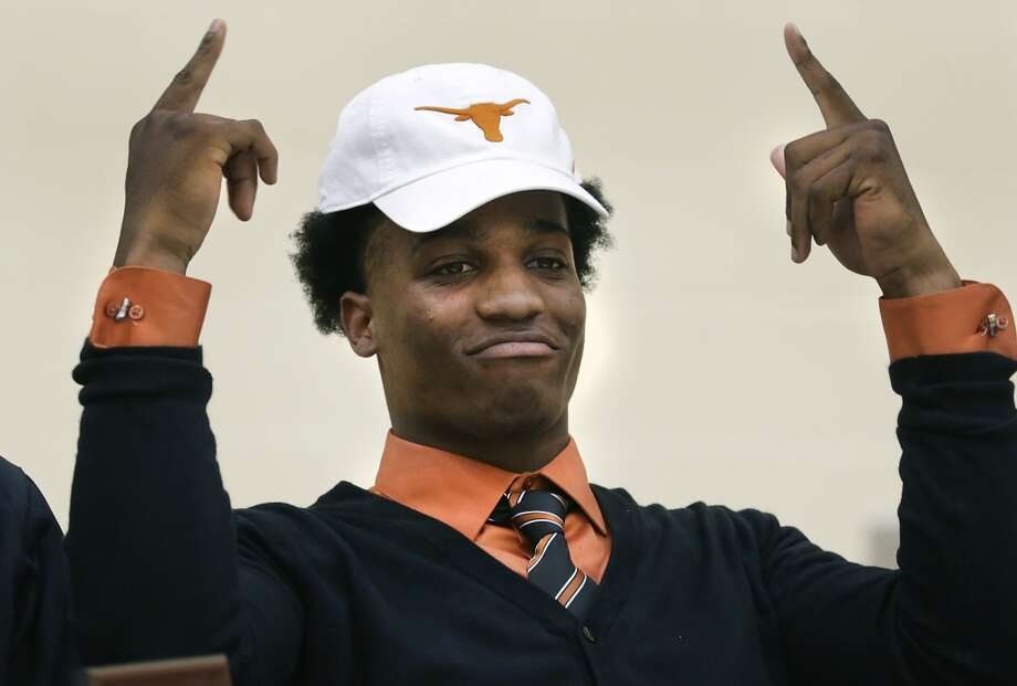 Derick Roberson, of Brennan High School, puts on a UT hat as he signs with the University of Texas football team.  Wednesday, Feb. 5, 2014. Photo: San Antonio Express-News