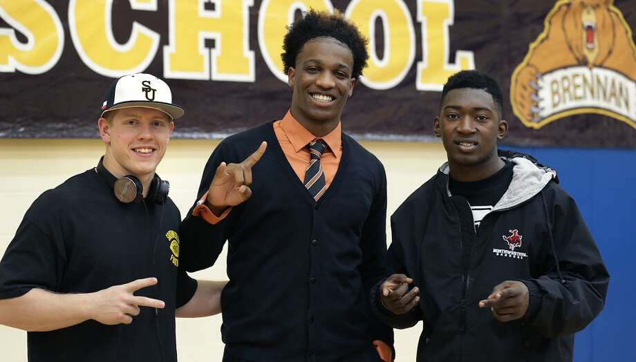 Derick Roberson, center, of Brennan High School, signs with the University of Texas football team.  Also signing from Brennan are Tanner Hanssen, left, going to Southwestern University and Nathaniel Wells Jr., right, going to Northwestern Oklahoma. Wednesday, Feb. 5, 2014. Photo: San Antonio Express-News