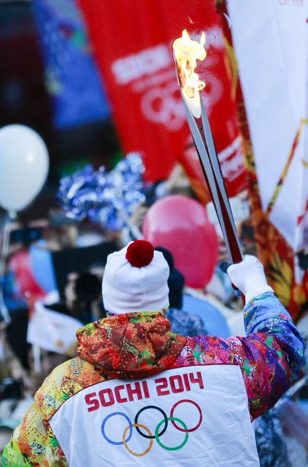 Alexey Voyevoda, a former Olympic bobsledder, who won silver in the 4-man bobsled in Turin in 2006, carries the Olympic torch as it makes it's way throughout the streets of the Rosa Khutor ski resort in Krasnaya Polyana, Russia at the Sochi 2014 Winter Olympics, Wednesday, Feb. 5, 2014. (AP Photo/Gero Breloer) Photo: Gero Breloer, Associated Press