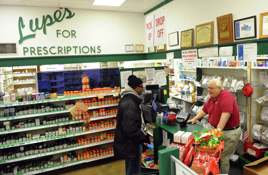 c466c2db4e Dan Lupariello, owner of Lupe's Pharmacy helps customer Rodney Bowens at  the pharmacy on Main