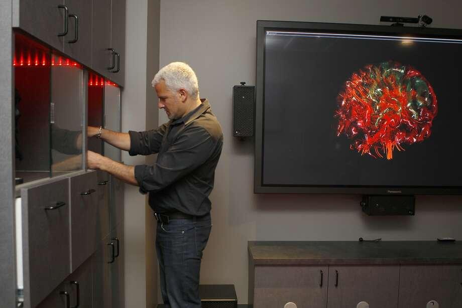 Dr. Adam Gazzaley, above, at UCSF's Neuroscience Imaging Center studying neural mechanisms and, below, wearing an EG cap. Photo: Liz Hafalia, The Chronicle