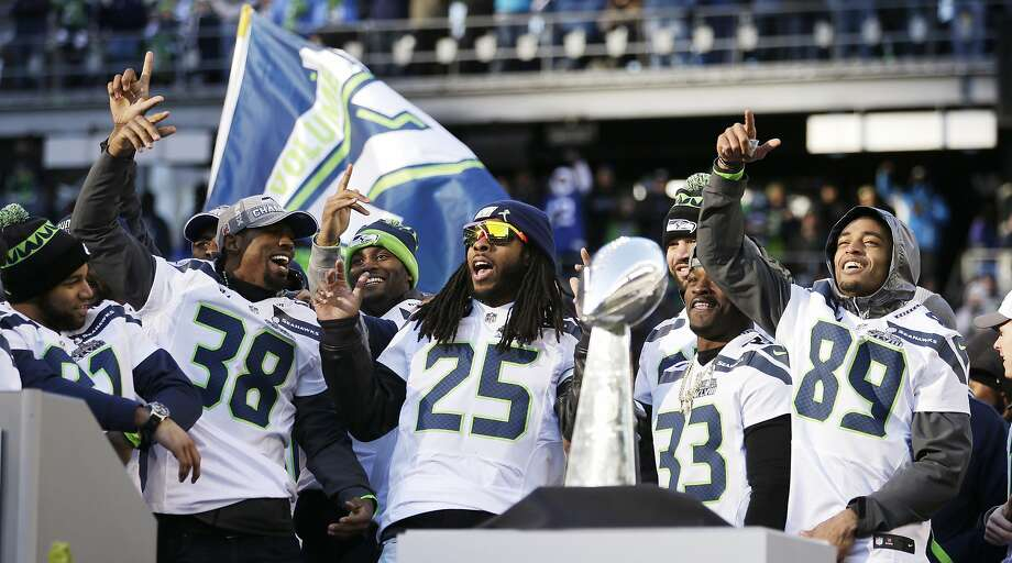 Seahawks players dance near the Vince Lombardi Trophy at CenturyLink Field rally after a parade for the Super Bowl champions through downtown Seattle. Photo: Elaine Thompson, Associated Press