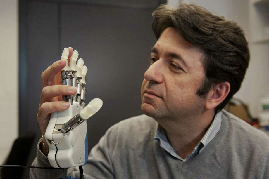 This undated handout photo provided by Science Translational Medicine shows neuroengineer Silvestro Micera, researcher at EPFL and Scuola Superiore Sant'Anna holding a bionic hand.  To feel what you touch _ that's the holy grail for artificial limbs. In a step toward that goal, European researchers created a robotic hand that let an amputee feel differences between a bottle, a baseball and a mandarin orange.  (AP Photo/Hillary Sanctuary, EPFL, Science Translational Medicine)  ORG XMIT: WX203 Photo: Hillary Adrienne Sanctuary / Science Translational Medicine