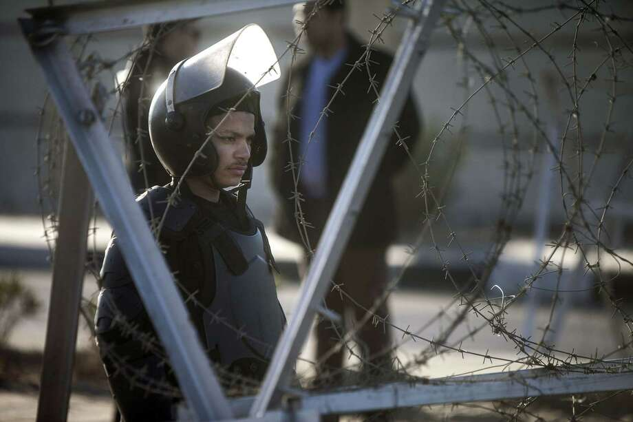 An Egyptian riot policeman stands gard behind barbed wire in front of the main gate of the Police Academy in Cairo where a new hearing in the trial of deposed president Mohamed Morsi resumed on February 5, 2014 on charges of inciting the killing of protesters, with the court scheduled to hear testimony of a former military commander. AFP PHOTO / MAHMOUD KHALEDMAHMOUD KHALED/AFP/Getty Images Photo: MAHMOUD KHALED / AFP