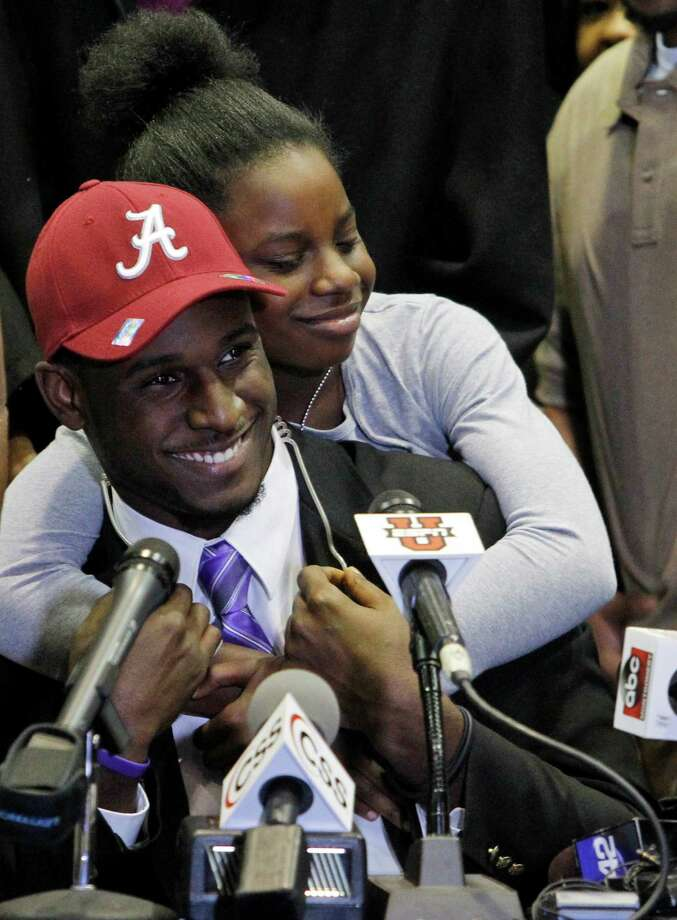 Rashaan Evans gets a big hug from his little sister, Ashley Evans, after the Auburn High School football player announced that he will attend Alabama during a national signing day ceremony on Wednesday, Feb. 5, 2014, in Auburn, Ala. (AP Photo/Butch Dill) ORG XMIT: ALBD107 Photo: Butch Dill / FR111446 AP