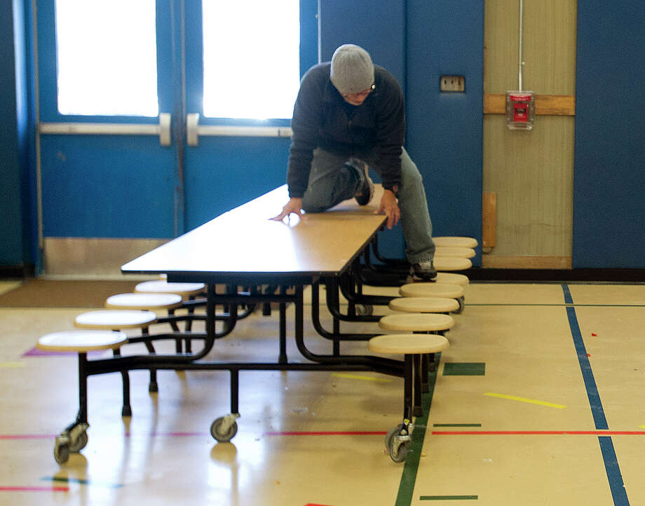 Manny Gil climbs on top of a cafeteria table to use his knee to pop the table into place so he can fold it after lunch at Springdale Elementary School in Stamford, Conn., on Thursday, January 30, 2014. Photo: Lindsay Perry / Stamford Advocate