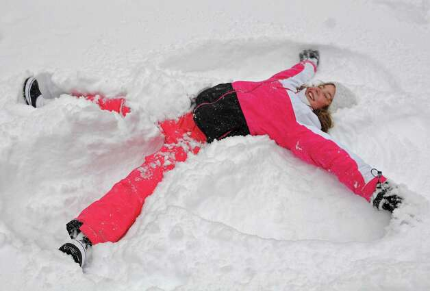 Zoe Conaway, 9, of Guilderland takes a break from sledding to make a snow angel in her front yard during Wednesday's snowstorm, Feb. 5, 2014, in Guilderland, N.Y.  (Lori Van Buren / Times Union) Photo: Lori Van Buren / 00025615A