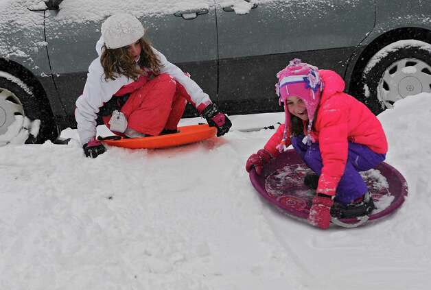 Zoe Conaway, 9, left, and her sister Natalie, 5, of Guilderland have fun sledding down a small hill in their front yard during Wednesday's snowstorm, Feb. 5, 2014, in Guilderland, N.Y.  (Lori Van Buren / Times Union) Photo: Lori Van Buren / 00025615A