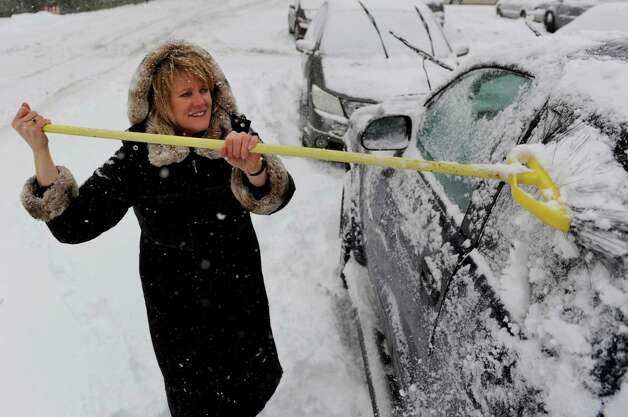 Barb Koper of Stillwater uses a broom to clear off the four-wheel-drive truck  Wednesday, Feb. 5, 2014, in Albany, N.Y. She borrowed the truck from her boyfriend to help her navigate through Wednesday's snowstorm. (Cindy Schultz / Times Union) Photo: Cindy Schultz / 00025615A
