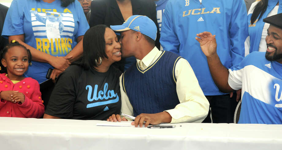 Aaron Sharp, center, of Summer Creek High School, plants a kiss on his mom, Kewanna Morris, while his sister, Ashley, 5, left, and step-father, Patrick Morris, right, look on after Sharp signed his letter-of-intent to play football at UCLA at the Humble ISD signing day event at the Humble Civic Center on Wednesday. Photo: Jerry Baker, Freelance