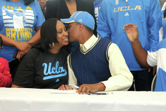 Aaron Sharp, center, of Summer Creek High School, plants a kiss on his mom, Kewanna Morris, while his sister, Ashley, 5, left, and step-father, Patrick Morris, right, look on after Sharp signed his letter-of-intent to play football at UCLA at the Humble ISD signing day event at the Humble Civic Center on Wednesday.