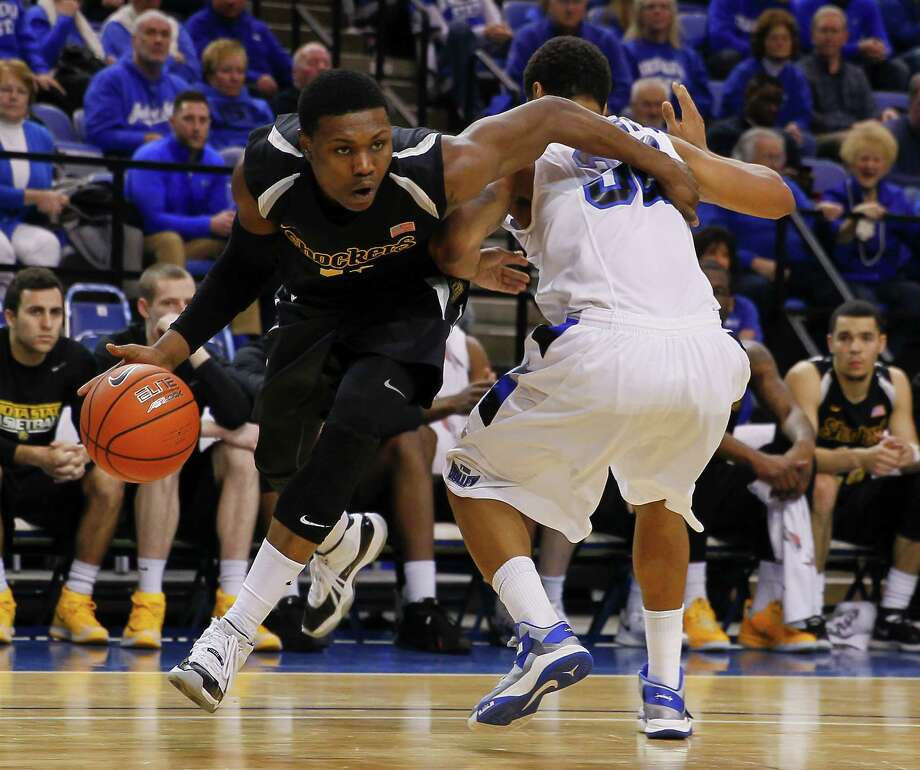 TERRE HAUTE, IN - FEBRUARY 05: Cleanthony Early #11 of the Wichita State Shockers reaches around Khristian Smith #32 of the Indiana State Sycamores and drives to the basket at Hulman Center on February 5, 2014 in Terre Haute, Indiana. Wichita State defeated Indiana State 65-58. (Photo by Michael Hickey/Getty Images) ORG XMIT: 466130459 Photo: Michael Hickey / 2014 Getty Images