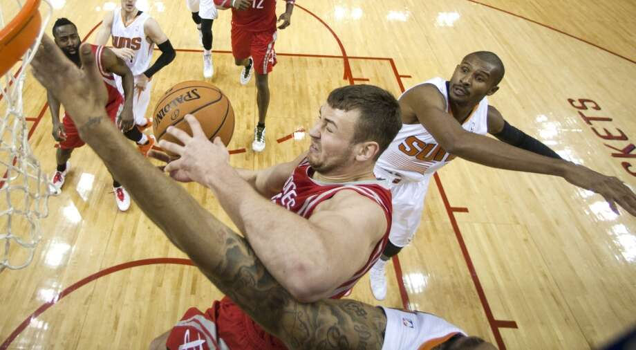 Donatas Motiejunas grabs a rebound away from Suns guard Leandro Barbosa. Photo: Brett Coomer, Houston Chronicle