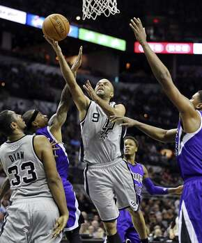 San Antonio Spurs' Tony Parker shoots between Sacramento Kings' Isaiah Thomas (left) and Sacramento Kings' Rudy Gay as San Antonio Spurs' Boris Diaw looks on during first half action Saturday Feb. 1, 2014 at the AT&T Center. Photo: Edward A. Ornelas, San Antonio Express-News