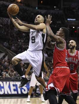 Spurs' Tony Parker (09) drives to the basket against Chicago Bulls' Jimmy Butler (21) in the first half at the AT&T Center on Wednesday, Jan. 29, 2014. Photo: Kin Man Hui, San Antonio Express-News