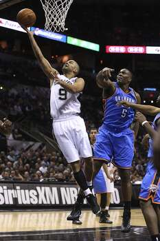 San Antonio Spurs' Tony Parker gets by Oklahoma City Thunder's Kendrick Perkins during the first half at the AT&T Center, Wednesday, Jan. 22, 2014. Photo: Jerry Lara, San Antonio Express-News