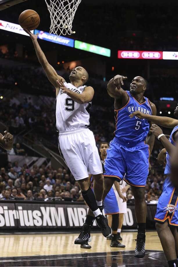 San Antonio Spurs' Tony Parker gets by Oklahoma City Thunder's Kendrick Perkins during the first half at the AT&T Center, Wednesday, Jan. 22, 2014. Photo: Jerry Lara, San Antonio Express-News